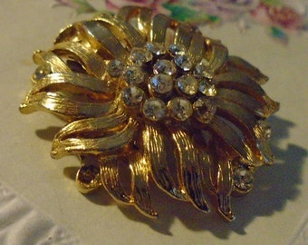 vintage goldtone round brooch with lots of sparkling clear stones