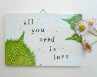 """ceramic plate with """"all you need is love""""-ceramic plate to hang with leaves and written-square ceramic-love"""
