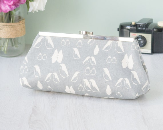 Evening clutch bag purse in grey and cream penguin print cotton fabric with silver metal kiss-lock straight frame.
