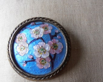 A beautiful French vintage enamel brooch showing cherry branches with blossoms