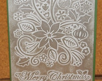Merry Christmas card embossed with holiday elements