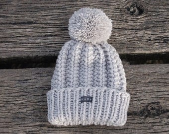 Silver grey sparkle womens HoBo 'Lofty' handmade bobble hat. Chunky hand knitted glitter beanie with large removable pom pom. Acrylic blend.
