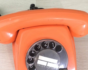 vintage orange rotary telephone , retro phone