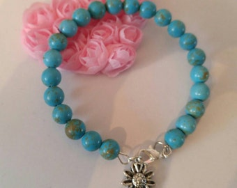 Unique Turquoise and silver bracelet with flower charm. Adult size made with memory wire. Lobster claw clasp.