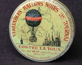 Black balloon. Vintage used French medicine round yellow box.