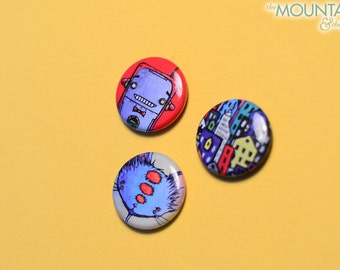 """Illustrated Button Pack – Three 1"""" Pinback Buttons – Robot, Cityscape & Cheshire Cat Set, Illustrations from Acrylic Paintings by Seth Jones"""