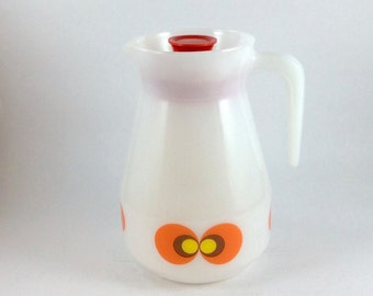 "Vintage opal glass pitcher. JENAer Glas by Schott, Mainz. Carina ""peacock eye"" design in orange, brown and yellow. Seventies."
