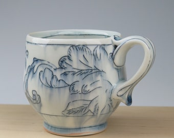 Handmade porcelain thrown mug with toile pattern and ornate handle