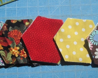 Hexi-Pack -- Set of 50 precut hexagons in various prints -- No 2 are the same -- These sides measure 2-1/4 inches. Die cut.