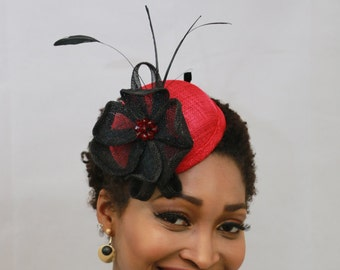 Red and black floral pill box hat with feathers
