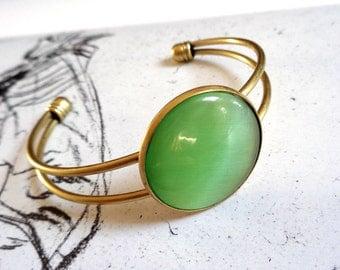 Bronze tone bangle bracelet cateye glass cabochon light green