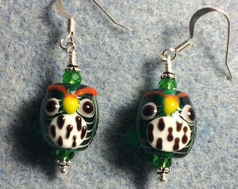 Emerald green and white spotted lampwork owl bead earrings adorned with emerald green Chinese crystal beads.
