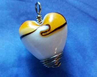 Gold and white heart shaped glass bead pendant, handwrapped in Gun Metal wire.