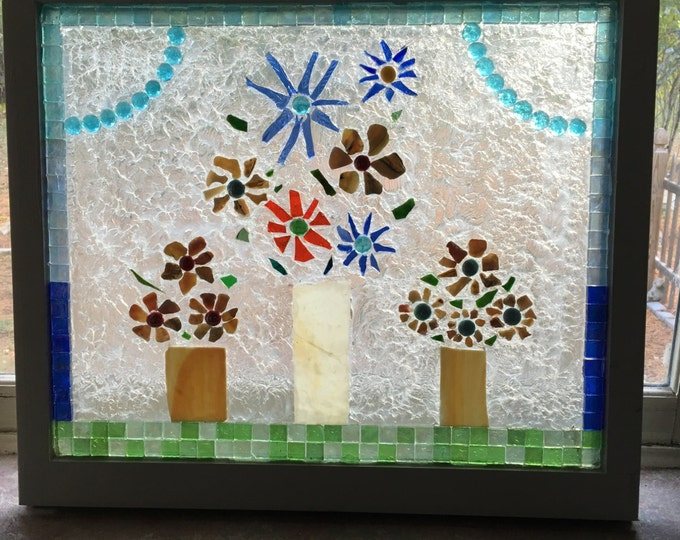 Old refurbished window designed with various pieces of glassware