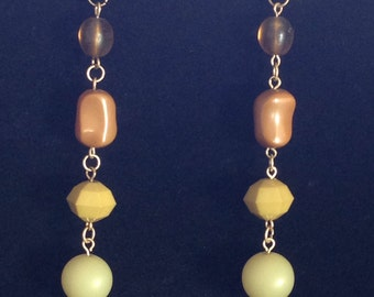 Green and brown beaded earrings .