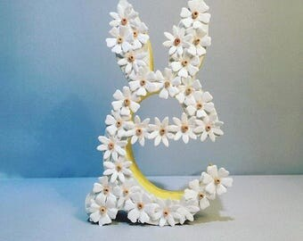 Bunny eared letter e with paper daisy themed decorations