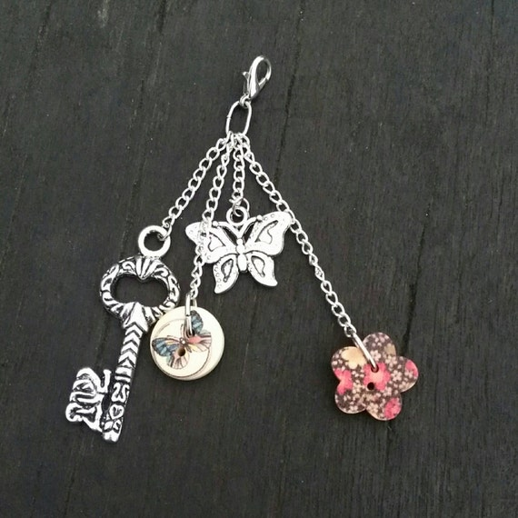 silver bag charm with butterfly and key charms with painted