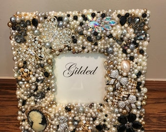 "Callie, 8"" square frame with a 3x3 opening. It is embellished with vintage jewelry, pearls and crystals."