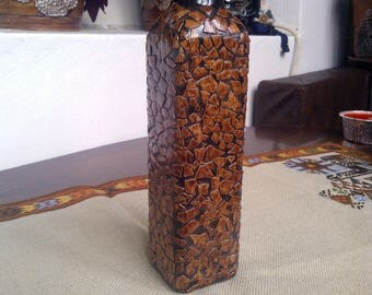Brown hand decorated bottle with eggshells