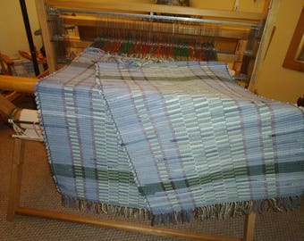 2 matching faded denim rugs with green tones and green stripes. One is 28-38, another 28x40.  Fringed