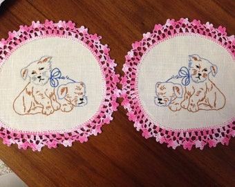 A pair of vintage hand embroidered 26cm doilies, puppy dogs, pink crochet edging