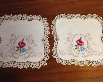 A pair of vintage hand embroidered doilies, 24 cm square, rose in a frame