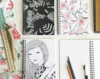 Spiral Notebook with lined pages and illustrated art covers