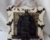 Creepy little haunted house cute kitsch bat sign says the word home on it