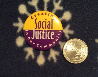 "Creating social justice in our community"" button purple/yellow"