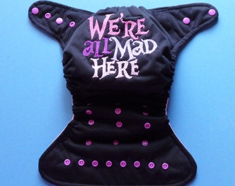 """SassyCloth one size pocket diaper with """"We're all mad here"""" embroidery on PUL. Made to order."""