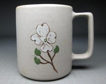 Pigeon forge pottery mug , dogwood decoration and yellow interior glaze .