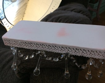 A pair of white metal distressed wall shelves with teardrop crystals