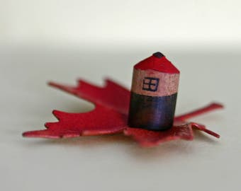 Miniature house sculpture on metal autumn leaf, red and brown, wood and metal, tiny, small sculpture, home, found item, pencil, fall