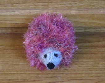 Hand-knitted hedgehog soft cuddly toy or mascot, made from eyelash yarn.