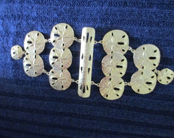 Large gold tone nautical sand dollar shoulder brooch by Ultra Craft