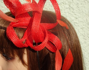 Coral red  fascinator made with sinamay loops and feather on silver headband.