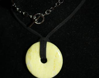 bright green stone donut pendent. black faux suede necklace