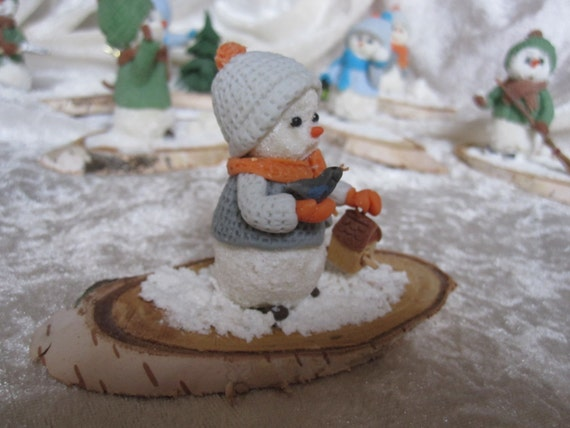 Snowman on its base natural wood. Porcelain cold saeljana. Christmas decoration, winter, holiday.