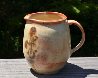 Ceramic hand thrown pitcher holds 18 ounces
