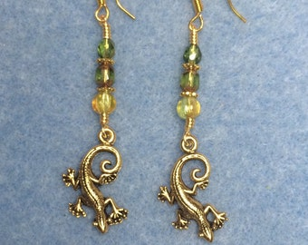 Tiny gold lizard charm earrings adorned with olive green Czech glass beads.