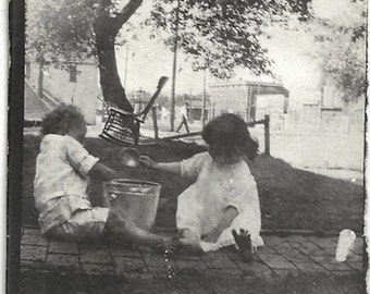 Old Photo Girl and Boy Playing with Pail on Brick Walkway Rocking Chair in Background 1920s Photograph Snapshot vintage