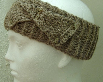 Crochet tan headband with flecks of black and a flat bow with buttons on the side