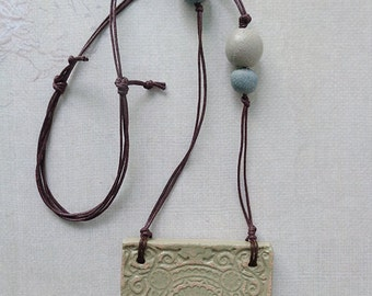 Light green ceramic handmade pendant with imprint. One of a kind necklace.