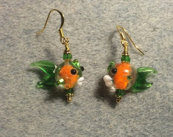 Orange and green glow in the dark lampwork fish bead earrings adorned with green Chinese crystal beads.