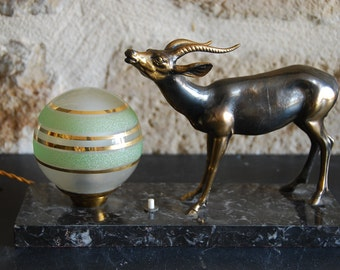 Vintage French bed side table light, black veined marble base, green and gilt glass globe light, spelter antilope. Good condition, complete.