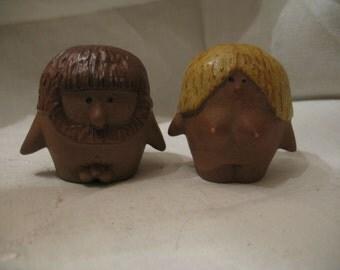 Salt & pepper shakers little prehistoric character. Ceramic boy girl.