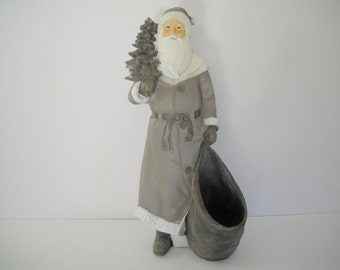Tall Santa Holding a Tree and a Bag (for a gift)