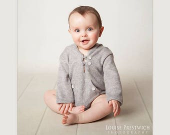 Baby Boy Newborn.In a grey stretch soft feel warm fabric.Two white pearlized buttons at the neck.Hooded with long sleeves and short legs.