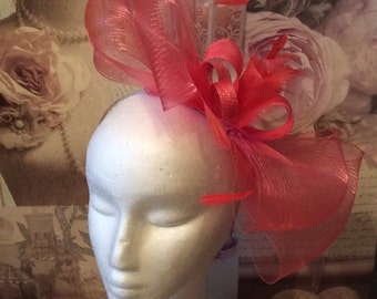 Coral pink medium size fascinator on headband.