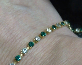 Green/white rhinestone tennis bracelet. Unmarked. Gold tone metal